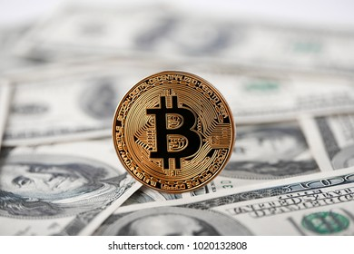 Shiny golden bitcoin lying on hundred dollar bills presenting biggest cryptocurrency and new futuristic form of money. Digital web electronic currency innovation blockchain mining exchange finance