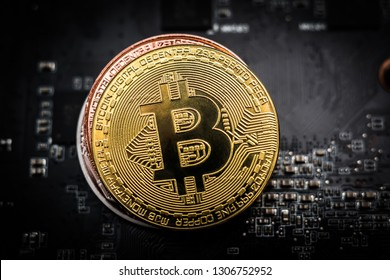 Shiny golden bitcoin on the top of a stack from bronze and silver bitcoin on computer board