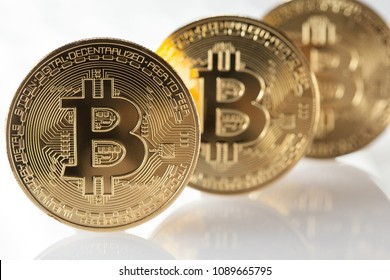 Shiny golden bitcoins on white background with reflection