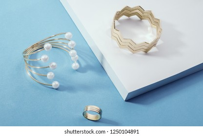 Shiny Golden bracelets and a ring on white corner on blue paper background  - Pearls bracelet and zigzag shape golden bracelet on white and blue display