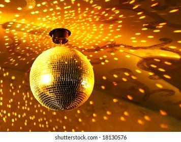 Shiny golden disco ball on nightclub