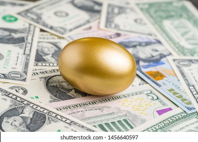 Shiny golden egg on pile of US America dollar banknotes money metaphor of finding the unbelievable good stock with high dividend or success investment in stock market concept.