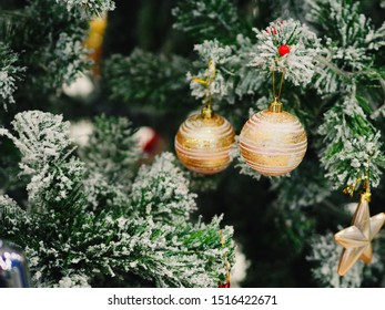 Shiny golden glister balls decorate on snow Christmas tree
