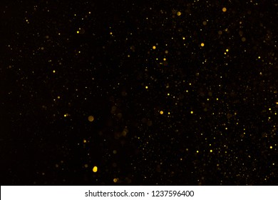 Shiny golden glitter particles falling on black background