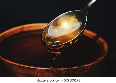 Shiny golden honey dripping off of a spoon into a wooden bowl with black background