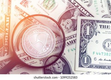 shiny golden NEM cryptocurrency coin on blurry background with dollar money 3d illustration