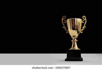 Shiny golden trophy cup with copy space on black background. Champion award for sports game competition or contest prize. Victory and Success concept. reward and pride of winner. great achievement.