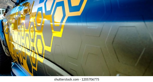 Shiny gray car with yellow geometric decals