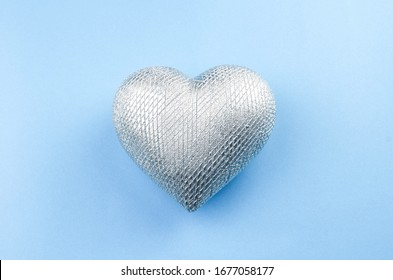 Shiny heart for your designs and projects. One of object top view, flat lay photo on the light blue background