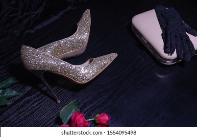shiny high heel shoes with a handbag on a dark table and on a black silk background