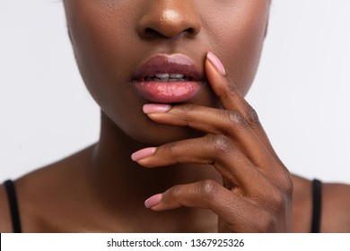 Shiny lip gloss. Close up of young African-American woman touching lips with shiny lip gloss