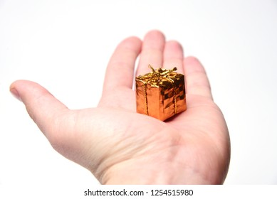 Shiny little gift in hand. Minimalism in the gift. Precious gift.