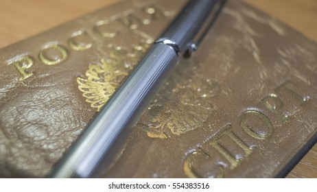 Shiny metal ball pen and a passport