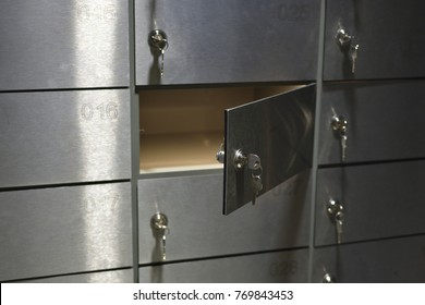 Shiny metal deposit boxes (safe cells) with numbers and keys in keyholes in a bank, one cell is opened, closeup