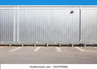 Shiny metal wall on a building with parking spaces in front