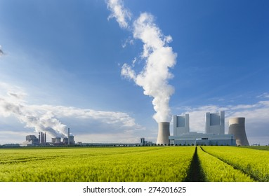 A shiny new lignite power station behind a rye field with wheel tracks leading to it and an old power station in the background