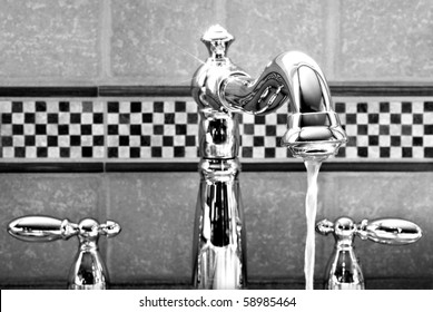 Shiny new stainless steel Victorian styled faucet with ceramic tile backsplash.  Black and white closeup with shallow dof.
