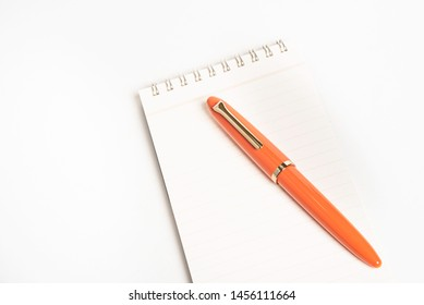 A shiny orange fountain pen together with a spiral-bound ruled notebook.