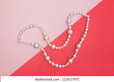 Shiny pearl necklace on pink background, looking like a smile.