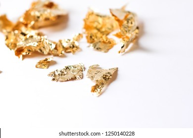 Shiny pieces of gold sweat or gold leaf lying on white background