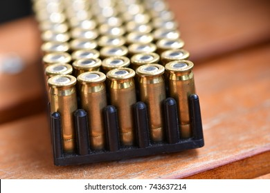 Shiny pistol ammunition on a wooden, brown table.