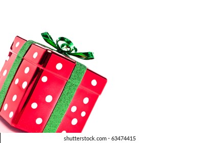 Shiny polka dot red and green Christmas present set on an angle with copy space