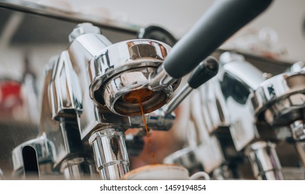Shiny portafilter attached to an espresso machine, busy pouring coffee into a white ceramic cup