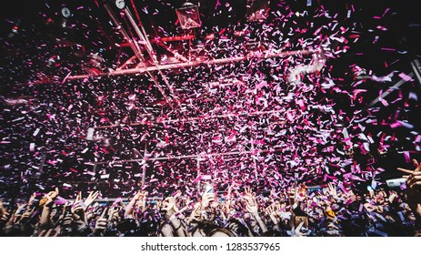 shiny purple confetti during the concert and the crowd of people silhouettes with their hands up