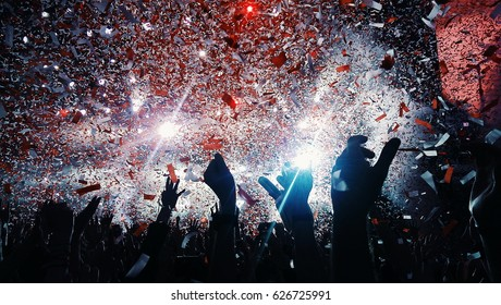 shiny rainbow confetti during the concert and the crowd of people silhouettes with their hands up. Dark background, smoke, concert  spotlights. Bright lights