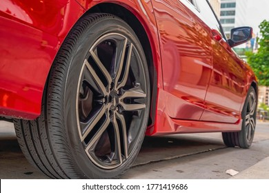 Shiny red car exterior with close up of the black rubber wheels against road
