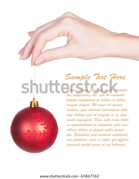Shiny red christmas tree ball  and girls hand on white background with copy space. Closeup with shallow dof.