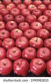 Pommes rouges délicieuses brillantes exposées, avec des gouttelettes d'eau