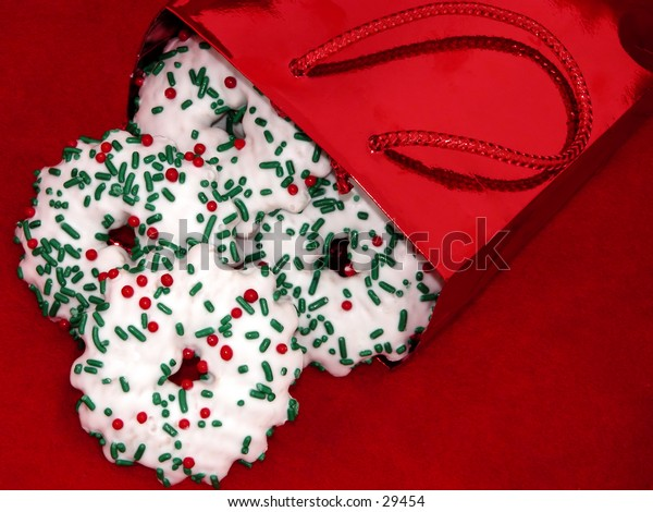 Shiny red foil bag spilling christmas gingerbread cookies out on red felt.