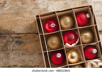 Shiny red and gold holiday ornaments in box on rustic table as seen from an overhead view