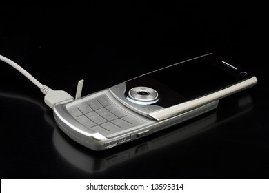 Shiny silver cell phone conected to charger - on shiny black background