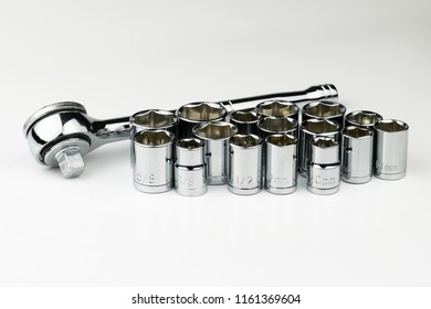 A shiny, silver, chrome socket wrench set with both SAE fractional sockets and metric sockets in millimeters on white background suitable for automobile mechanic, repairman, or construction.