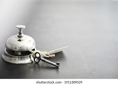 A shiny silver metal bell at hotel reception. A table in the hotel at the concierge with a bell and a door key. Key and bell in a hotel.