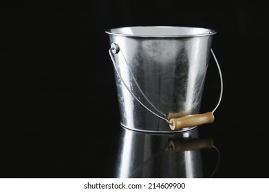 Shiny silver metal bucket with a wooden handle on a black background with a reflection and copyspace