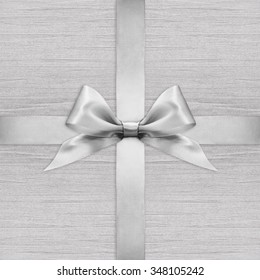 Shiny silver satin ribbon bow on argent background