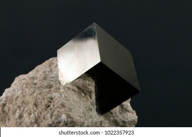 Shiny smooth regular shape pyrite cube on a dark background