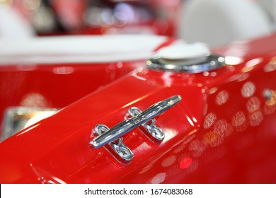Shiny stainless mooring cleat on red plastic motor boat deck close up, marine equipment