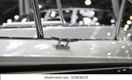 Shiny stainless mooring cleat on white motor boat deck close up, marine equipment