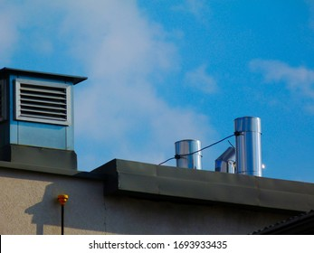 shiny stainless steel sheet mechanical air vents, ducts on flat roof. building engineering, heating, cooling and  building ventilation system. lightning protection and grounding. blue sky, white cloud