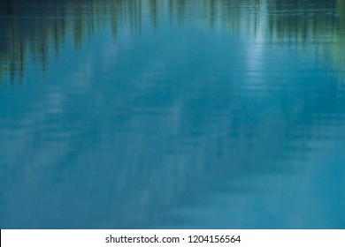 Shiny texture of surface of mountain lake. Background with reflection of green mountains with tops of conifer trees in clear water in sunny day under blue sky. Coniferous forest reflected in water.