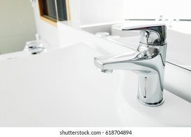Shiny water tap faucet on bathroom sink.