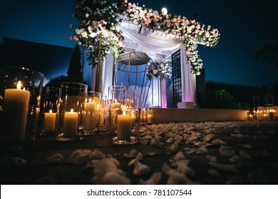 Shiny white candles stand on the ground in the darkness before wedding altar
