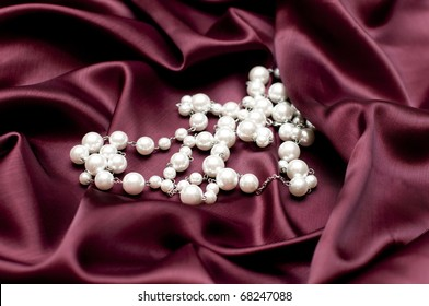shiny white pearls on ruby satin background