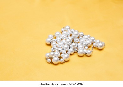 shiny white pearls on yellow satin background
