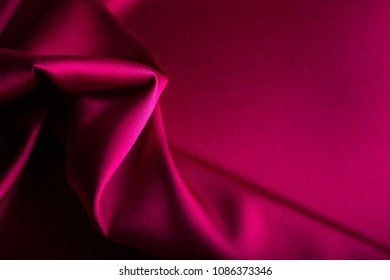Shiny wine red satin curved in various lines.