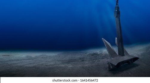 Ship anchor underwater on bottom in clean ocean water at anchorage. Marine shipping  			 and diving surveys concept.